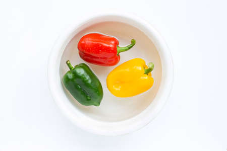 Bell pepper soaked in water. Washing fresh vegetables on white background. Фото со стока
