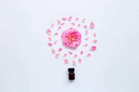 Bottle of rose essential oil for aromatherapy on white background.