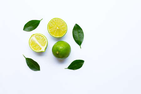 Ripe limes with green leaves on white background.