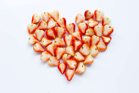 Strawberries positioned in a heart shape on white background