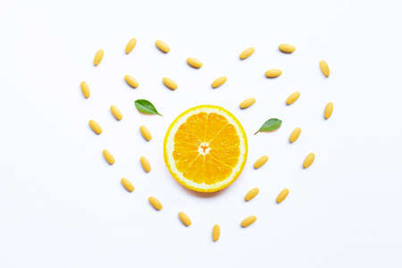 Vitamin C pills with orange fruit on white background