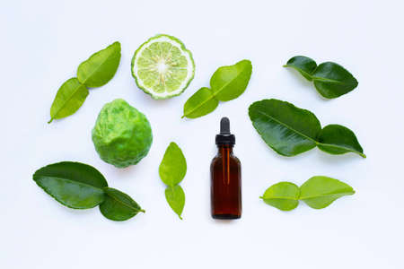 Bottle of essential oil and fresh kaffir lime or bergamot fruit with leaves isolated on white background.