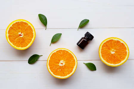 Orange essential oil with fresh orange citrus fruit and green leaves on white wooden background. 版權商用圖片