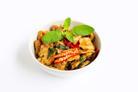 Stir-fried hot and spicy pork with basil on white background.