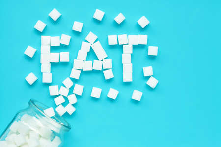 Cubes of sugar on a blue background. Fat text from sugar cubes. Top view Imagens