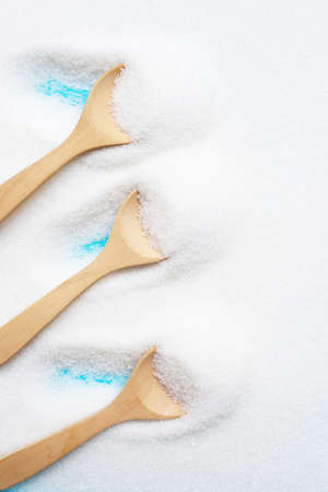 Wooden spoon with white granulated sugar. Top view
