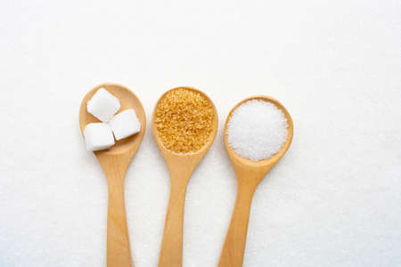 Wooden spoon with various types of sugar on white granulated sugar background. Top view