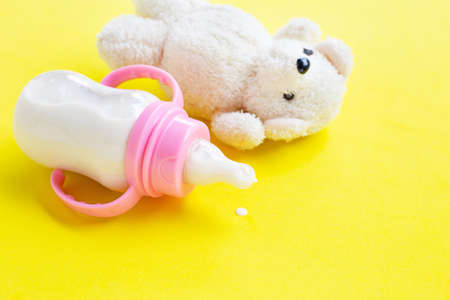 Bottle of milk for baby with toy white bear on yellow background.  Copy space