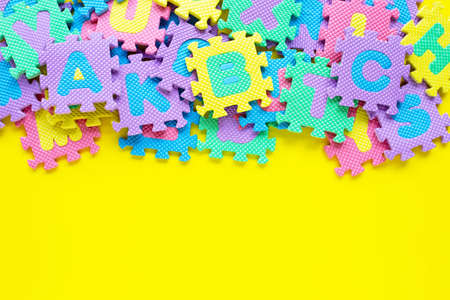 Alphabet puzzle on yellow background. Top view Imagens