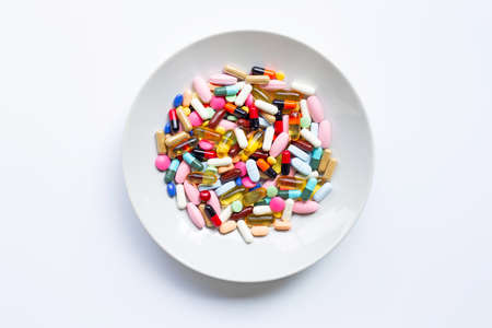 Colorful tablets with capsules and pills on white dish on white background.