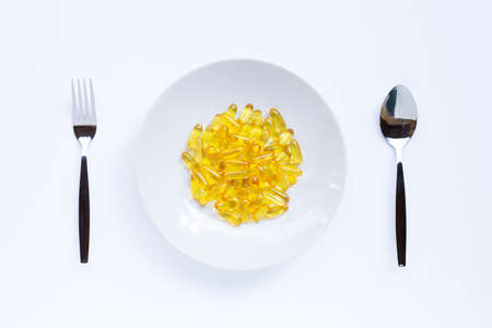 Fish oil capsules on white dish, folk and spoon on white background.