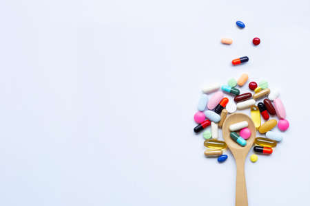 Colorful tablets, capsules and pills with wooden spoon on white background.