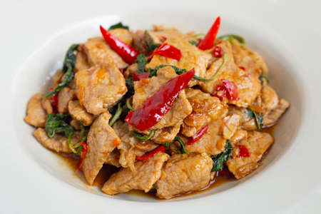 Stir-fried hot and spicy pork with holy basil on white background. Foto de archivo
