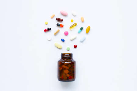 Colorful tablets with capsules and pills on white background.