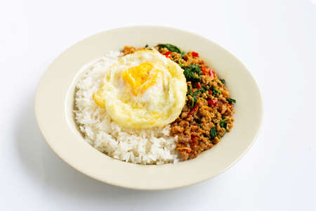 Rice topped with stir-fried pork with holy basil and fried egg, white background. Imagens