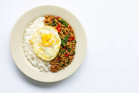 Rice topped with stir-fried pork with holy basil and fried egg, white background.