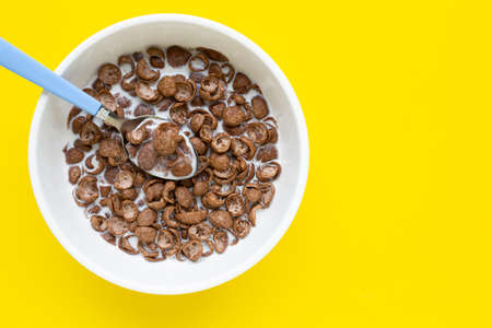 Chocolate cereal with milk on yellow background. Top view