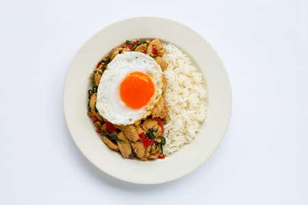 Arroz cubierto con pollo salteado y albahaca santa, huevo frito, fondo blanco. Foto de archivo