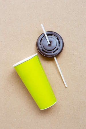 Green paper coffee cup with straw and plastic cap on plywood background.