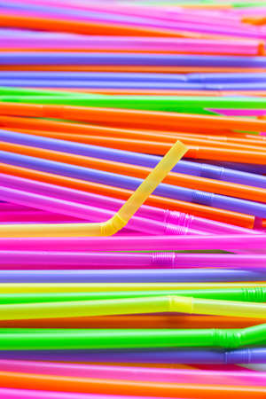 Colorful plastic straws background. Plastic waste pollution.