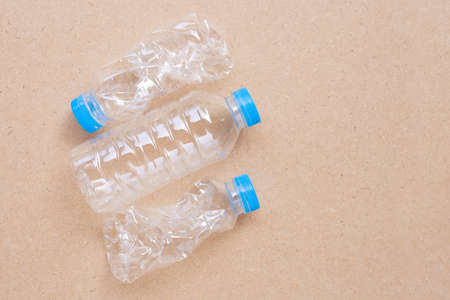 Plastic bottles on plywood background. Copy space