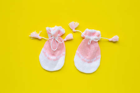 Baby gloves on yellow background. Top view