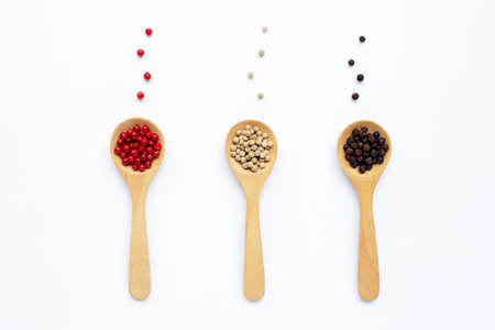 Black, red and white peppercorns with wooden spoon on white background.