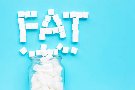 FAT Cubes of sugar on a blue background. Copy space Banco de Imagens