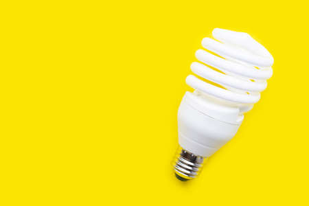 Energy saving light bulb on yellow background. Copy space