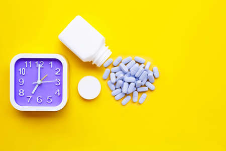 Clock with PrEP ( Pre-Exposure Prophylaxis). used to prevent HIV on yellow background. Copy space
