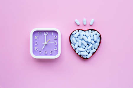 Clock with PrEP ( Pre-Exposure Prophylaxis). used to prevent HIV on pink background. Top view 스톡 콘텐츠