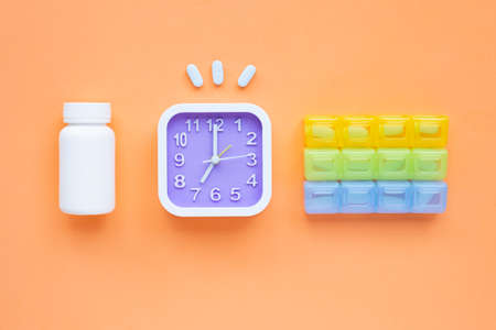 Clock with PrEP ( Pre-Exposure Prophylaxis). used to prevent HIV on orange background. Top view 스톡 콘텐츠