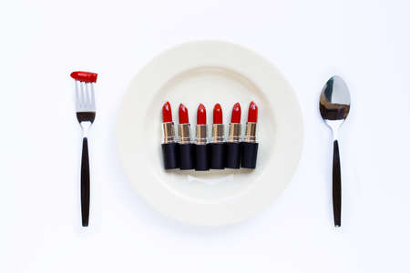 Lipsticks on white dish with fork and spoon on white background. 写真素材