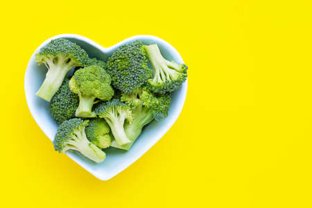 Fresh broccoli in a heart shaped bowl on yellow background. Copy space 写真素材
