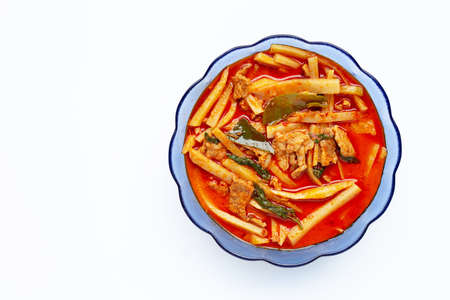 Red curry preserved bamboo shoot with pork, white background.