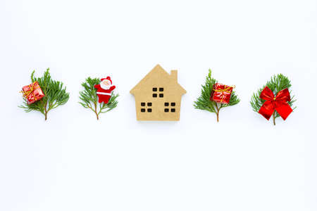 Merry Christmas and Happy Holidays, Miniature house with Christmas composition. gifts, pine branches and decorations on white background. Copy space 写真素材