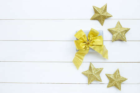 Merry Christmas and Happy Holidays, Christmas composition. gift box, golden stars on white wooden background. Top view