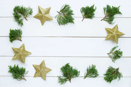 Merry Christmas and Happy Holidays, Christmas composition frame made of golden stars, pine branches  on white wooden background. Top view