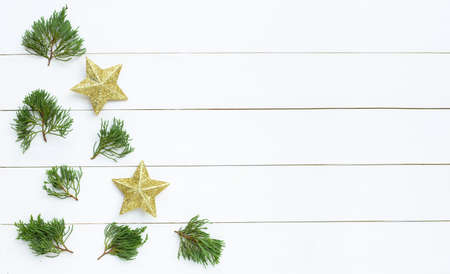Merry Christmas and Happy Holidays, Christmas composition. golden stars, pine branches on white wooden background. Top view