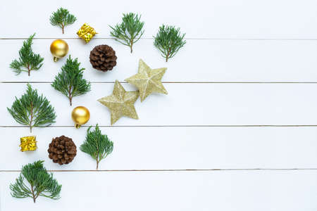 Merry Christmas and Happy Holidays, Christmas composition. golden stars, pine branches and decorations on white wooden background. Top view 写真素材