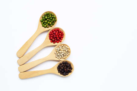 Green, red white and black peppercorns with wooden spoon on white background.