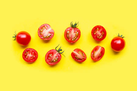 Fresh tomatoes, whole and half cut isolated on yellow background. Top view