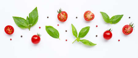 Fresh  cherry tomatoes with basil leaves and different type of peppercorns on white background. Top view Banco de Imagens