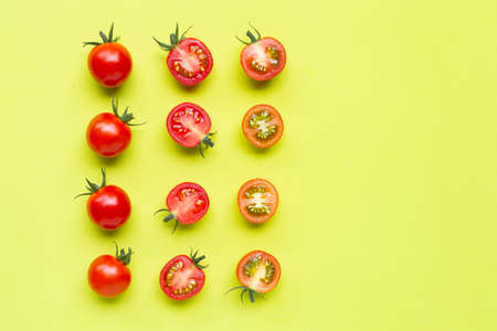 Fresh tomatoes, whole and half cut isolated on green background. Top view