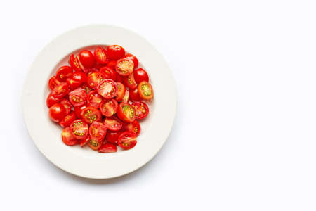 Fresh tomatoes, half cut on white dish.  Copy space