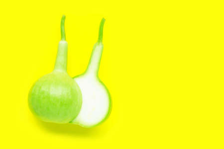 Calabash, Bottle Gourd fruit yellow background. Copy space