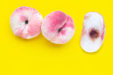 Chinese flat peaches on yellow background. Copy space 写真素材