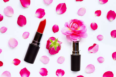 Lipstick with rose petals isolated on white background.