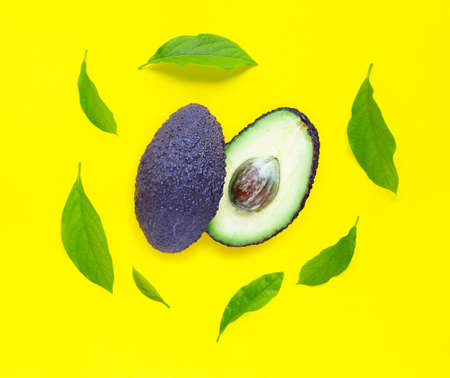 Avocado  with leaves on yellow background. Top view 写真素材