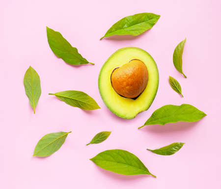 Avocado  with leaves on pink background. Top view